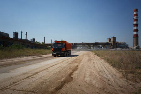 dumptruck: A huge orange tip truck with a shadow driving on a road on a natural background. Huge transporter in a sandy quarry. Stock Photo