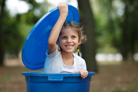Girl in blue recyling waste bin have fun inside. Concept of environmental protection. Colorful boxes. Stock Photo