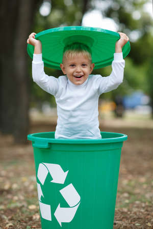 Boy have fun inside recyling waste bin outside. Concept of environmental protection. Colorful boxes. Stock Photo