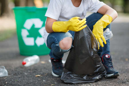 Male hands in yellow rubber gloves putting household waste into small and black bin bag outside.