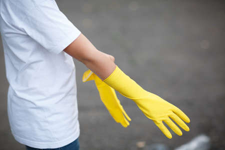 Wearing latex glove for cleaning on hand isolated on asphalt background. Rubbish on the back side.