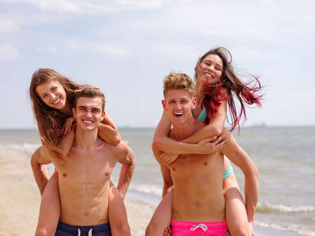 firstlove: Boys, carrying a their girls on back, at the beach, outdoors. Close-up image of cheerful happy couples.