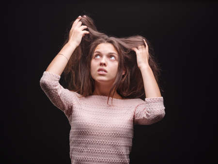 Shocked female pulling her sick hair on a black background. Gorgeous woman unhappy with her hair. Hair routine concept.