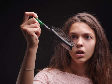 Girl struggling with tangled hair on the black background. Close-up woman looking at a comb with hair. Balding concept.