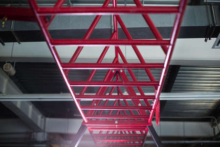 magnesia: Close-up of crimson cylindrical metal, steel bars that are rigidly held above and parallel to the floor on a light silver background, equipment for sports competitions. Stairway for sports exercises.