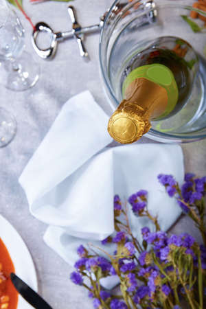 A close green bottle of champagne, little violet flowers, silvery corkscrew, glasses, a white plate with canned beans, snow-white napkin on a blurred light background. Stock Photo