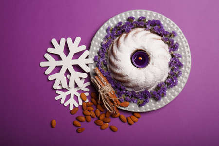 Top view of a plate with a round cake covered with powdered sugar and decorated with little flowers, almond, sticks ok cinnamon and white snowflakes on a bright violet background. Christmas concept. Stock Photo