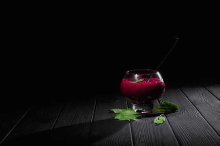 A claret-colored beet smoothie cocktail in a big transparent dessert glass. A glass filled with healthy vegetable cocktail on a black table background. A beet beverage with green leaves. Copy space. Stock Photo