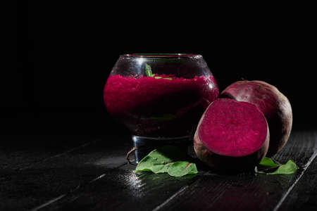 A big, fancy glass filled with saturated red beetroot juice on a black wooden background. Ripe and peeled beets for a healthful summer salad. Raw vegetable cocktails. Copy space. Stock Photo