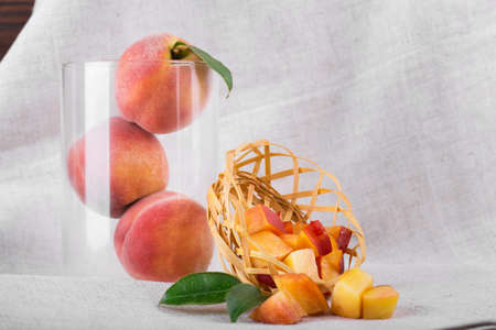 A composition of ripe peaches with green leaves on a gray fabric background. A close-up of three whole fruits in a transparent vase next to a basket full of cut peaches. Tropical fruits for desserts.