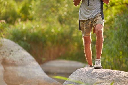 Homme voyage snikers sur le paysage de la nature. Fortes jambes de randonnée au sommet de la montagne. Mâles voyageurs de voyage sur le paysage de la nature. Randonneur en bonne santé à travers la terre rocailleuse. Banque d'images - 86986069