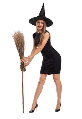 Aantrekkelijk heksenmeisje met een bezem die op een witte achtergrond wordt geïsoleerd. Halloween kostuums concept.
