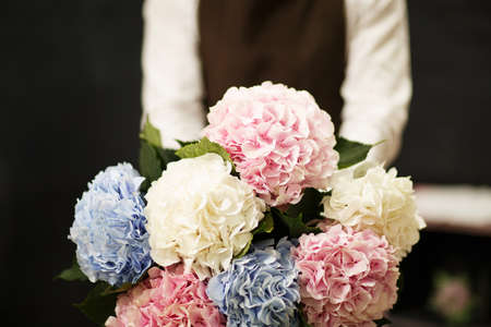 Close-up of man with bouquet on a blurred background. Florist with blooming flowers. Blossom concept.