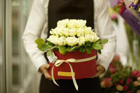 Close-up of florist holding flowers on a blurred background. Man presenting a bouquet. Decor concept. Stock Photo