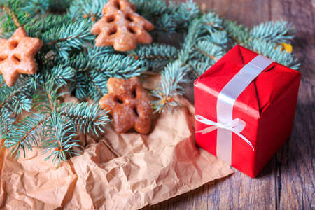 celebrate: Gift box, cookies and pine branch on a table background. Red present box. Christmas concept. Stock Photo