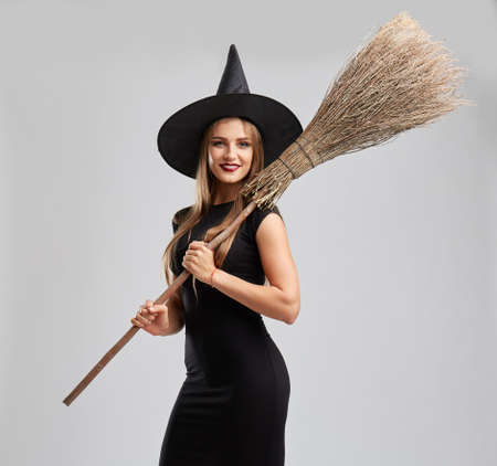celebrate: Pretty, sexy young girl in a witch costume with a broom on a light background. Halloween party concept.