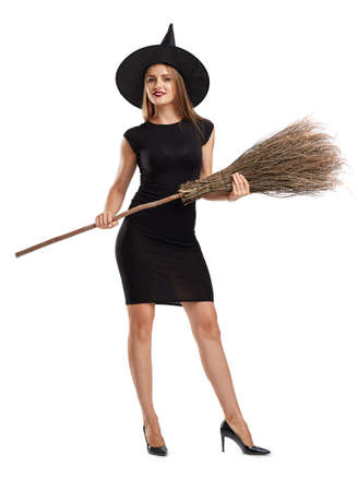 celebrate: Pretty, sexy young girl in a witch costume isolated on a white background. Halloween party concept. Stock Photo