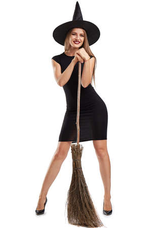 celebrate: Attractive witch girl with a broom isolated on a white background. Halloween costumes concept.