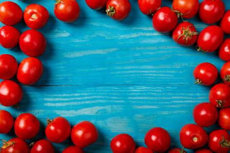 Top view of colorful, fresh tomatoes on a blue wooden background. Italian cafe, restaurant. Copy space.