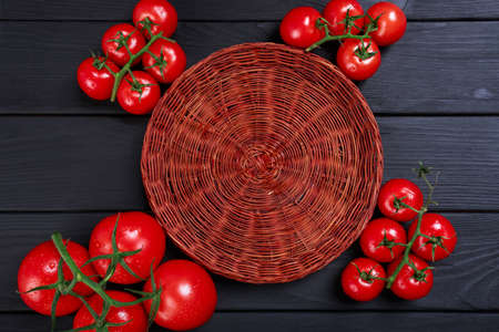 Top view of a composition of colorful tomatoes and wicker basket on a black table background. Traditional autumn agriculture veggies.