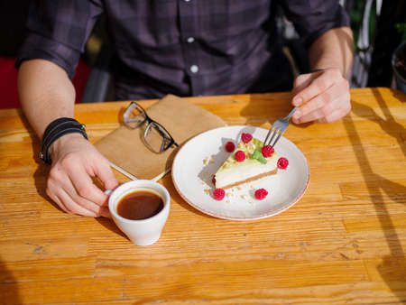 Young male hands and tasty cupcake with raspberries cup of cofe with milk and tablet on the wooden table.Business concept. Stock Photo