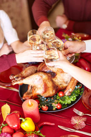 Close-up family clinking glasses on Thanksgiving on a table background. Cheers with champagne. Celebration concept. Archivio Fotografico