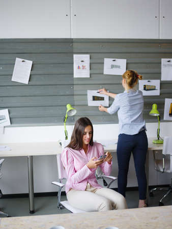 work life balance: Beautiful young woman working in the office grey wall with scraps on the background. Business concept. Stock Photo