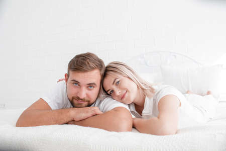 sexual intimacy: Sensual young couple together in bed. Happy couple in bedroom isolated on a white background.