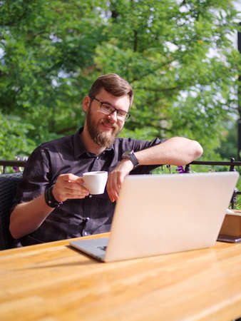 work life balance: Goodly young man working on laptop while sitting outdoors . Business concept. Stock Photo