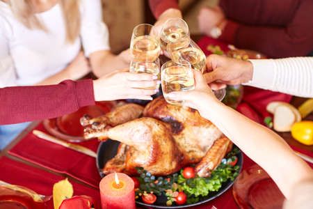 Close-up family clinking glasses on Thanksgiving on a table background. Cheers with champagne. Celebration concept. Stock Photo