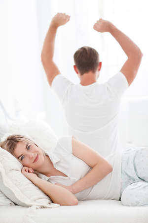 Sensual young couple together in bed. Happy couple in bedroom isolated on a white background.