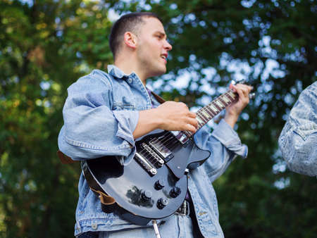 Young guy sings songs and plays guitar on a jeans jacket in a park on a natural background. Music concept.