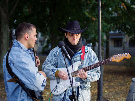 Happy young guys sings songs and plays guitar on a jeans jacket in a park on a natural background. Banque d'images