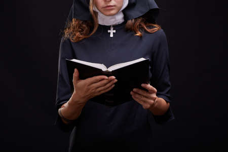 Pretty young nun in religion concept against dark background.
