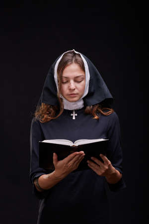 Pretty young nun in religion concept against dark background.