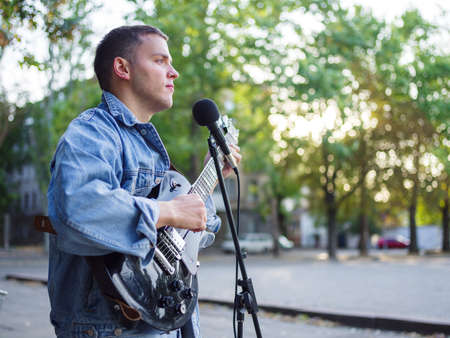 Young guy sings songs and plays guitar on a jeans jacket in a park on a natural background.