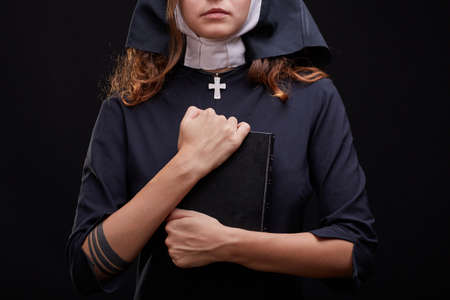 Pretty religious nun in religion concept against dark background. Stock Photo