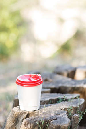 White cup of coffee on a stump in a park on a nature background.