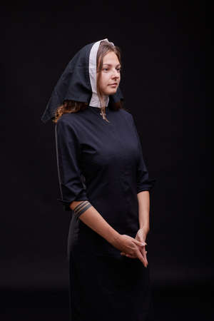 Pretty religious nun in religion concept against dark background. Stock Photo