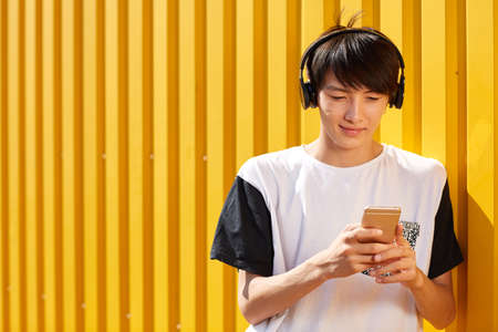 bakground: Young man listening to music on a yellow bakground. Music player concept. Copy space.