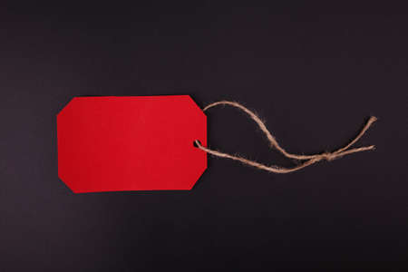 Close-up of a bright red tag, on a black background. For a black Friday. Stock Photo