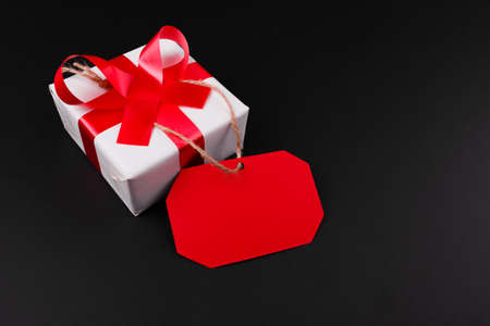 Close-up of red tag is attached to a white gift box with a red ribbon on a black background. Stock Photo