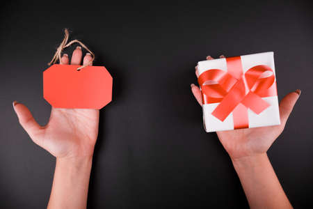 desprecio: Close-up of female hands holding a red tag and a gift box on a black background. Foto de archivo