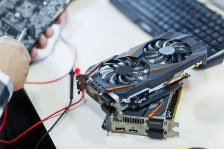 Close-up of a man who repairs a video card. Cryptocurrency. Business and finance concept.