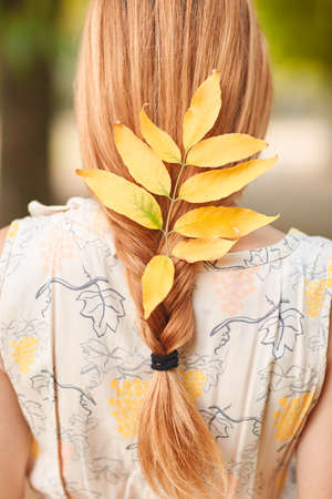 Close-up of a young girl plaited dry autumn leaves in beautiful red hair. Stock Photo