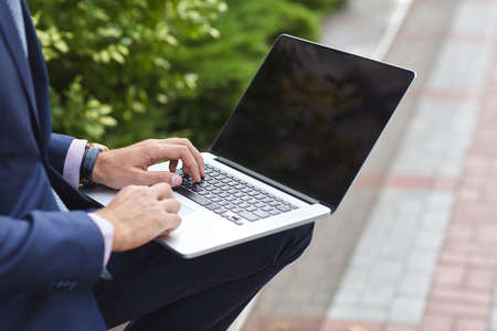 clock: Close-up of a businessman in a blue suit who works for a laptop outdoors in the park. Stock Photo