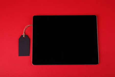 Close-up on a bright red background with the left is a black tag, with the right tablet lying. Black Friday Stock Photo