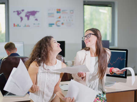 white sheet: Two cheerful beautiful young business girls in the office. Stock Photo