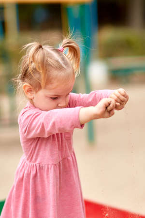 pies bonitos: Little girl in pink dress playing with sand