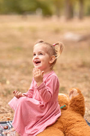 Funny little girl in pink dress shows tongue.